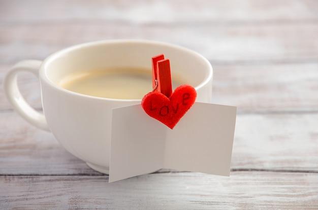 Tasse frischer morgenkaffee mit valentinstagkarte.