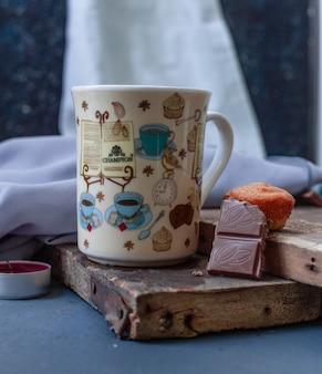 Tasse getränk, eine tafel schokolade und ein muffin auf dem holzstück