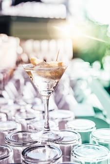 Tasse gin tonic mit einer zitronenscheibe und oliven.