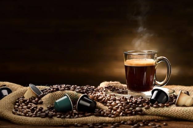 Tasse glas kaffee mit rauch und kaffeebohnen und kaffeekapseln auf leinensack auf altem holztisch