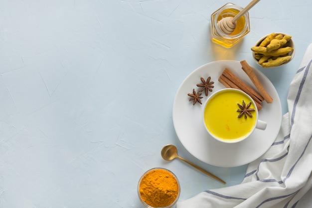 Tasse goldene kurkuma-milch mit honig. gesundes getränk für immunität. draufsicht. natürliches essen