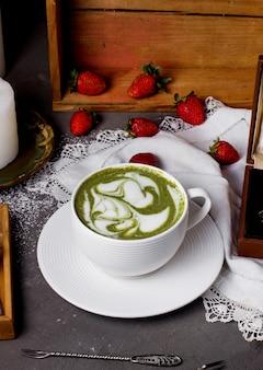 Tasse grüner kaffee und erdbeeren auf dem tisch