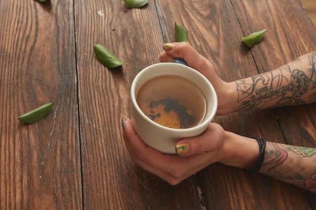 Tasse grüner tee in weiblichen händen auf einem holztisch