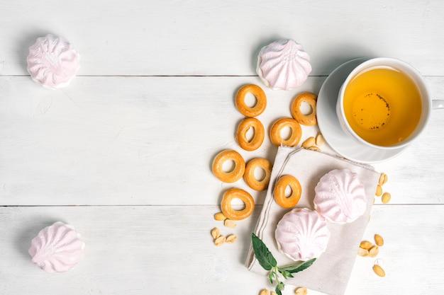 Tasse grüner tee mit süßigkeiten, draufsicht. bagels, nüsse und zarte marshmallows an einem licht