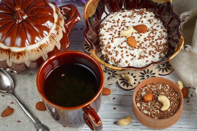 Tasse grüner tee, quark plus haferflocken, leinsamen, nüsse und honig