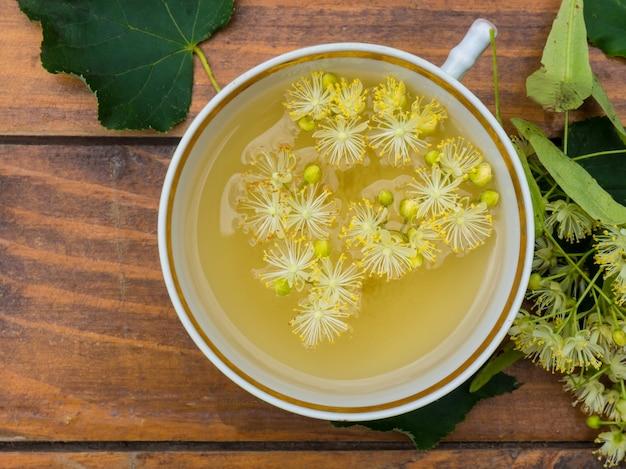 Tasse grüner tee und linde auf holzhintergrund, nützliches lindenblüten-volksmedizinkonzept
