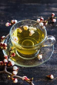 Tasse grüner tee und pfirsich blühenden zweig