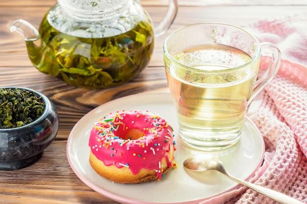 Tasse heiße getränke des grünen tees mit dem donut glasiert