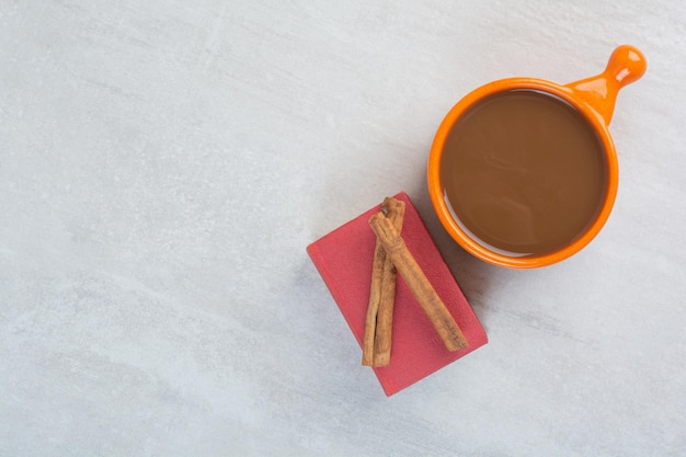 Tasse heiße schokolade, buch und zimt auf grauem hintergrund. foto in hoher qualität