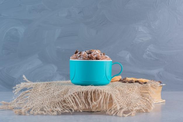 Tasse heiße schokolade mit geschnittenen trockenfrüchten auf buch.