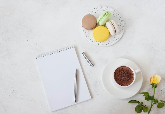 Tasse heiße schokolade mit macarons, blume und notizblock