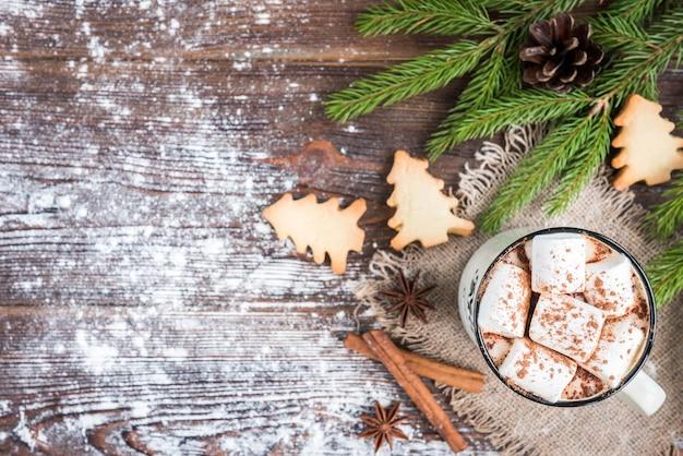 Tasse heiße schokolade mit marshmallow, gewürzen, weihnachts-ingwerplätzchen, tannenzweigen und zapfen auf dunklem hölzernem hintergrund. kopieren sie platz für text. weihnachtstapete, karte.