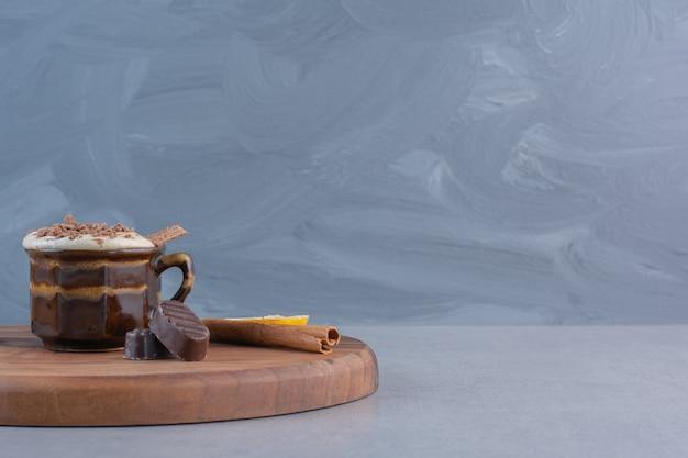 Tasse heiße schokolade und leckere snacks auf holzbrett.
