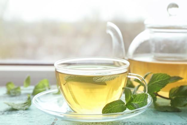 Tasse heißen aromatischen tee mit zitronenmelisse auf fensterbank