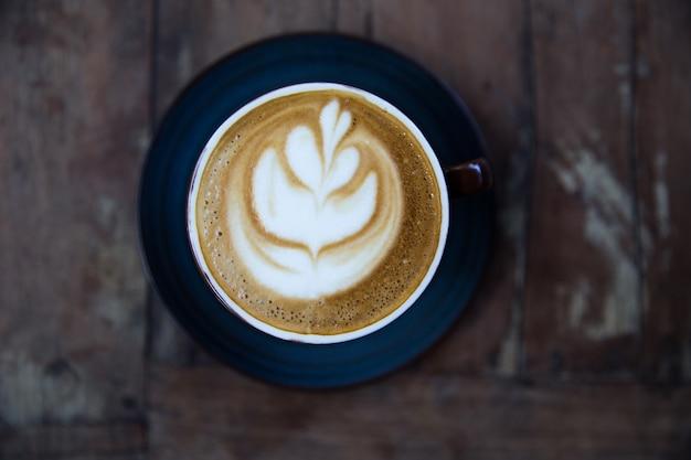 Tasse heißen cappuccino auf holztischhintergrund mit latte art. ansicht von oben.