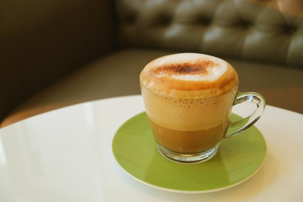 Tasse heißen cappuccino-kaffee serviert auf weißem runden tisch mit verschwommenem sofa