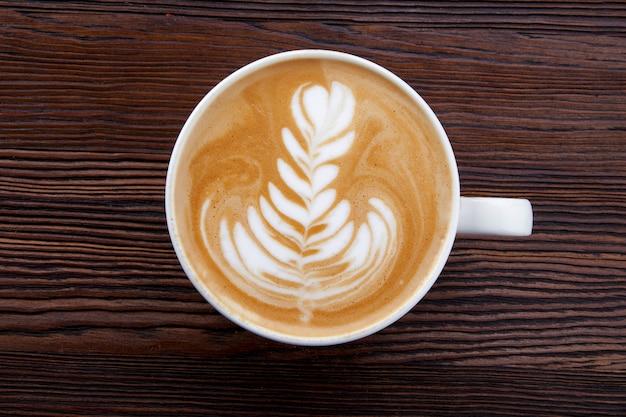 Tasse heißen cappuccino mit muster auf holzuntergrund