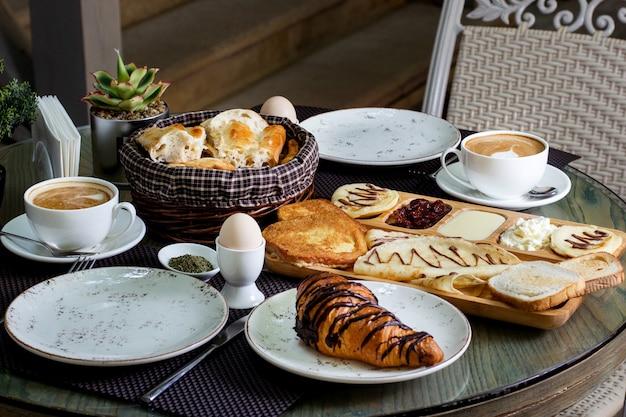 Tasse heißen cappuccino und schokoladencroissant zum frühstück