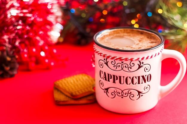 Tasse heißen cappuccino und weihnachtsdekoration