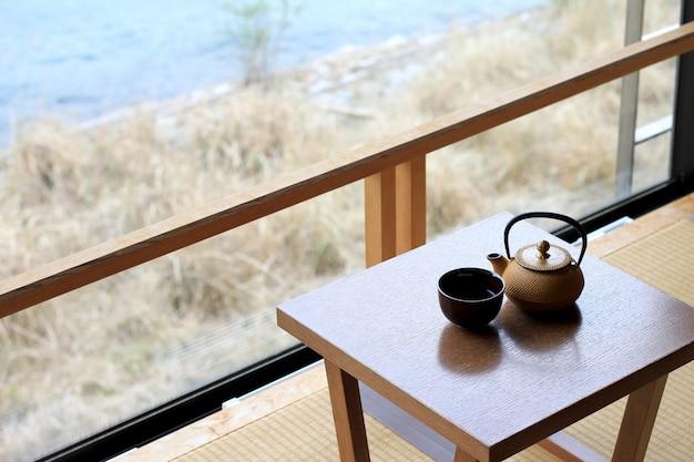 Tasse heißen grünen tee und teekanne auf einem tisch