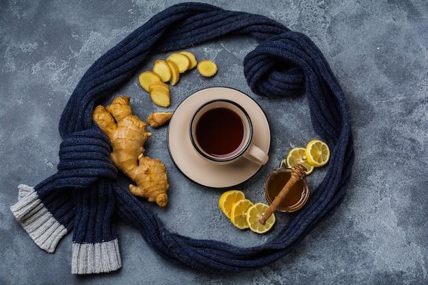 Tasse heißen ingwertee mit zitrone und honig auf dunkelgrauer oberfläche