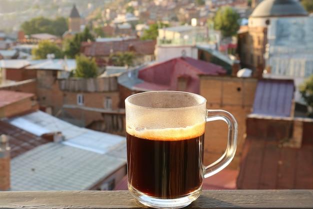 Tasse heißen kaffee auf der terrasse mit verschwommenem blick auf die stadt im hintergrund