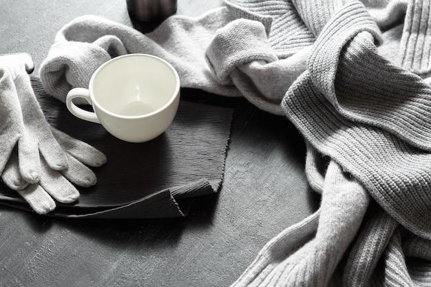 Tasse heißen kaffee auf einem schwarzen tisch mit warmem pullover