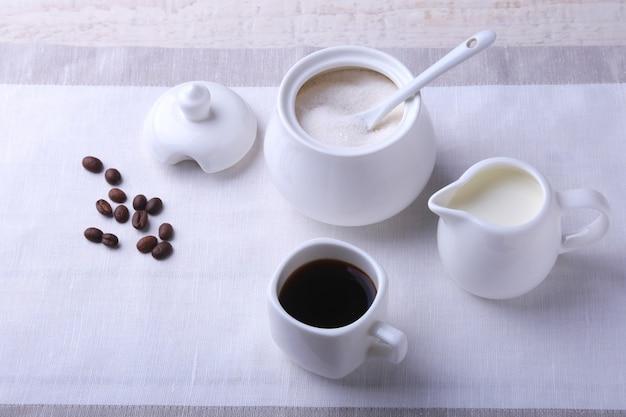 Tasse heißen kaffee espresso, kaffeebohnen, krug milch und schüssel mit zucker. kaffee-konzept.