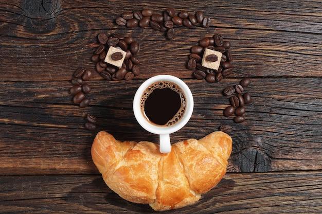 Tasse heißen kaffee mit croissant auf altem holztisch, ansicht von oben