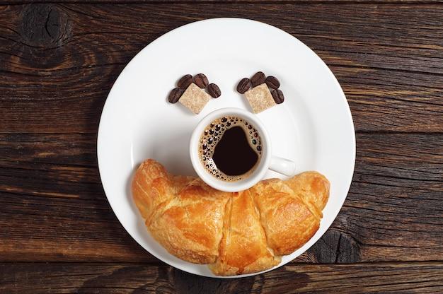 Tasse heißen kaffee mit croissant im teller auf altem holztisch, ansicht von oben