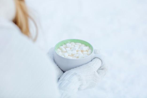 Tasse heißen kaffee mit marshmallow in den händen in weißen handschuhen auf dem hintergrund des schnees nahaufnahme