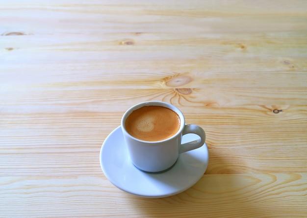 Tasse heißen kaffee serviert auf einem holztisch im morgenlicht