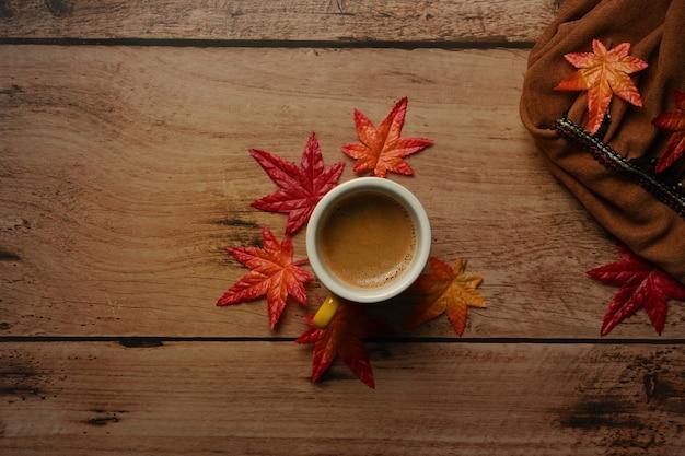 Tasse heißen kaffee und ahornblätter auf holztisch. herbstsaisonkonzept.