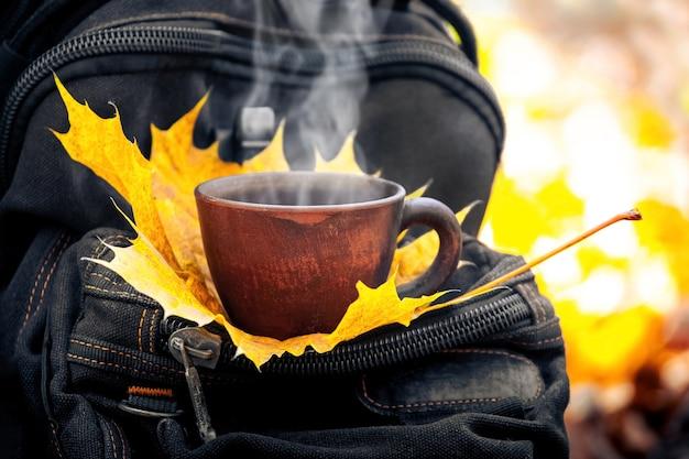 Tasse heißen kaffee und ahornblatt auf einem rucksack im herbstwald