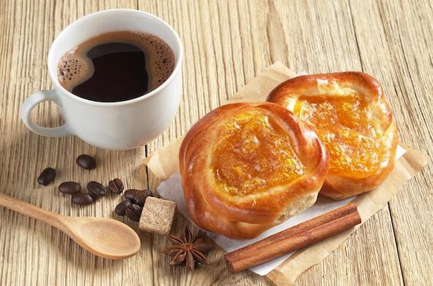 Tasse heißen kaffee und brötchen mit aprikosenmarmelade auf holzuntergrund