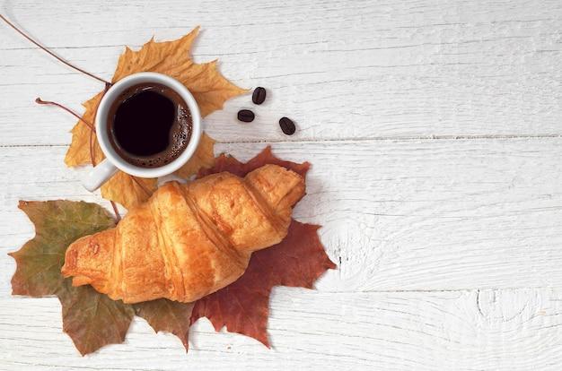 Tasse heißen kaffee und croissant auf weißem holztisch mit herbstlaub, ansicht von oben