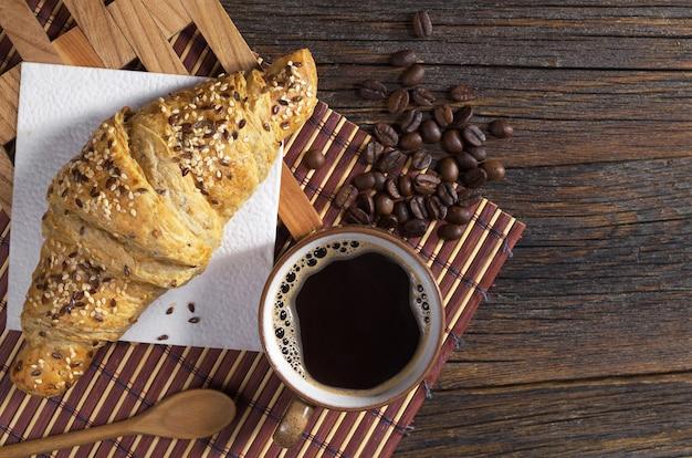 Tasse heißen kaffee und croissant mit sesam zum frühstück auf dunklem holztisch, ansicht von oben