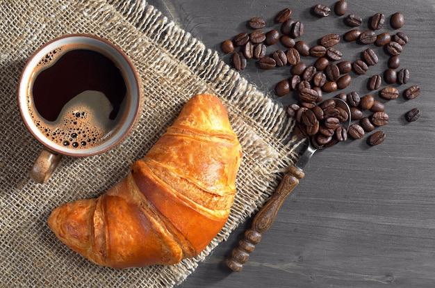 Tasse heißen kaffee und frisches croissant auf dunklem holztisch, ansicht von oben