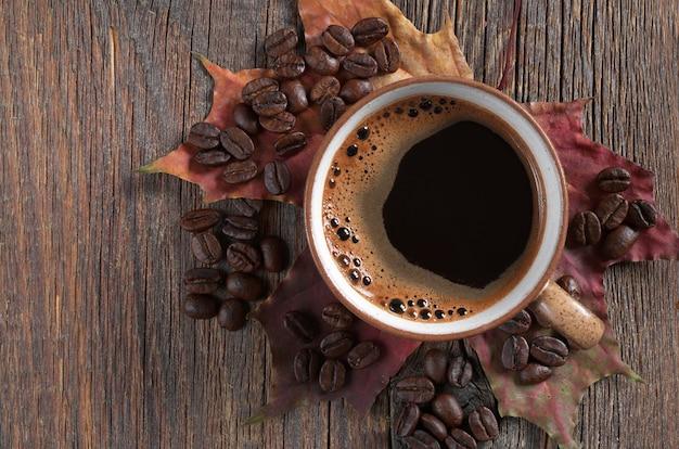 Tasse heißen kaffee und herbstahornblätter auf dunklem holzhintergrund, ansicht von oben