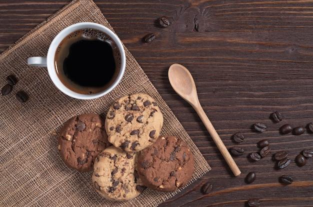 Tasse heißen kaffee und kekse mit schokolade und nüssen auf braunem holztisch, ansicht von oben