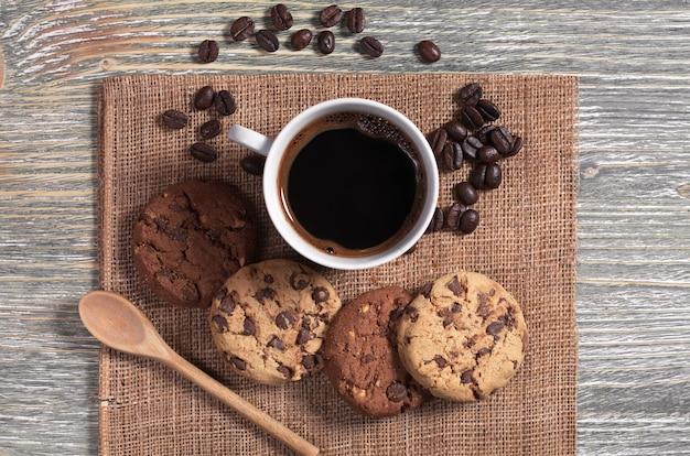 Tasse heißen kaffee und kekse mit schokolade und nüssen auf rustikalem holztisch, ansicht von oben