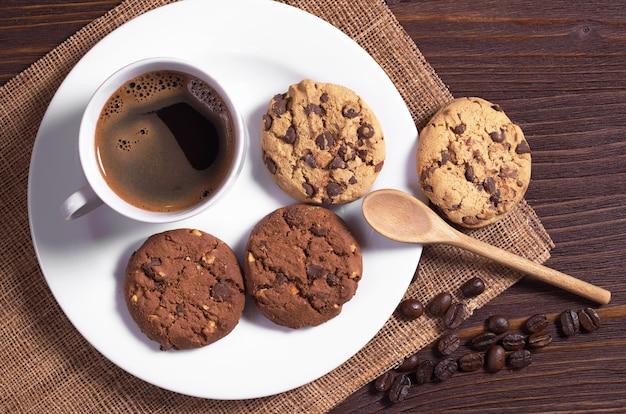 Tasse heißen kaffee und kekse mit schokolade und nüssen in der platte auf braunem holztisch, ansicht von oben