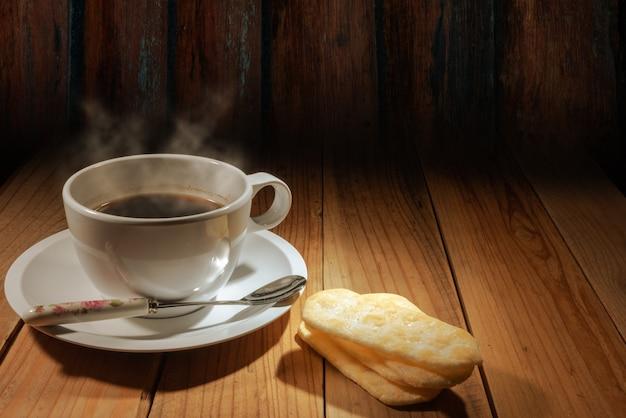 Tasse heißen kaffee und reis süßigkeiten auf log-wand