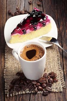 Tasse heißen kaffee und süßer kuchen mit beeren auf dunklem holztisch