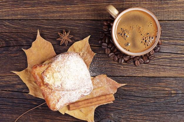 Tasse heißen kaffee und süßes brötchen auf altem holztisch. ansicht von oben