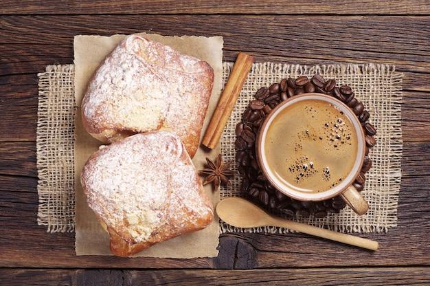 Tasse heißen kaffee und zwei frische brötchen auf dunklem holztisch. ansicht von oben