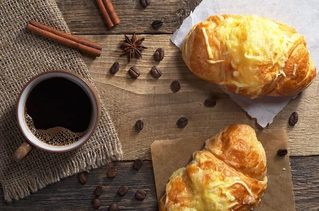Tasse heißen kaffee und zwei frische croissants mit käse auf altem holztisch, ansicht von oben