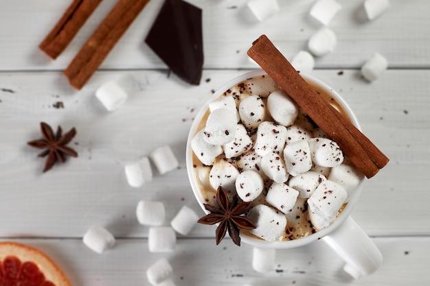 Tasse heißen kaffees mit marshmallows, bestreut mit schokolade, anis, zimt und einer scheibe getrockneter grapefruit auf weißem holztisch. draufsicht.