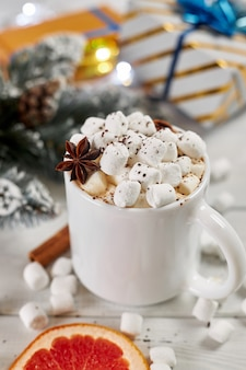 Tasse heißen kaffees mit marshmallows, bestreut mit schokolade, anis, zimt und einer scheibe getrockneter grapefruit auf weißem holztisch. weihnachtskonzept. heißes wintergetränk und geschenkboxen.