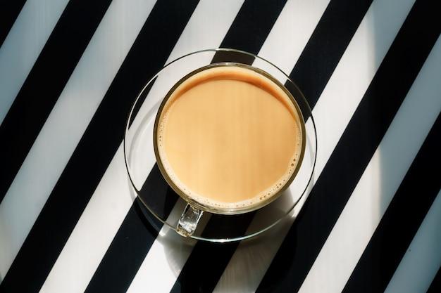 Tasse heißen kaffees mit milch auf einem schwarz-weiß gestreiften hintergrund. speicherplatz kopieren